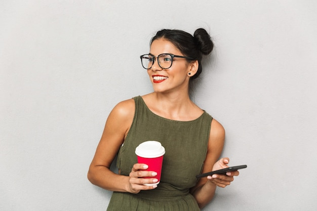 Portrait of a smiling young woman isolated, using mobile phone, holding takeaway coffee cup