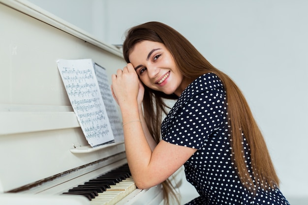 Portrait of a smiling young woman leaning on the piano looking to camera