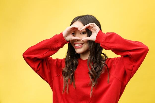 Портрет улыбается молодая женщина, делая знак сердца руками.