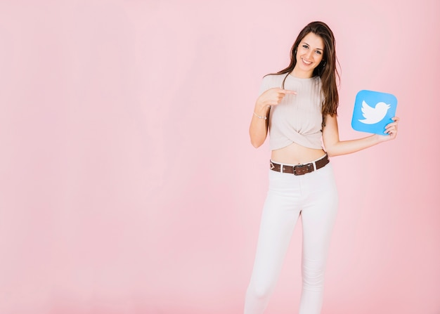 Portrait of a smiling young woman pointing at twitter icon