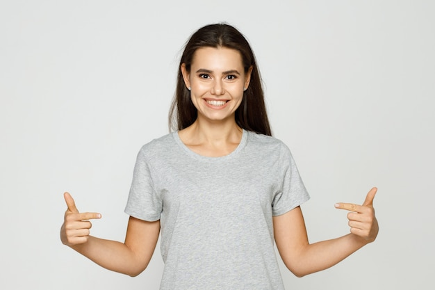 Portrait smiling young woman points her finger at copy space on tshirt