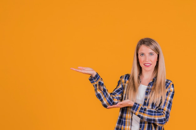 Portrait of a smiling young woman presenting something against an orange backdrop