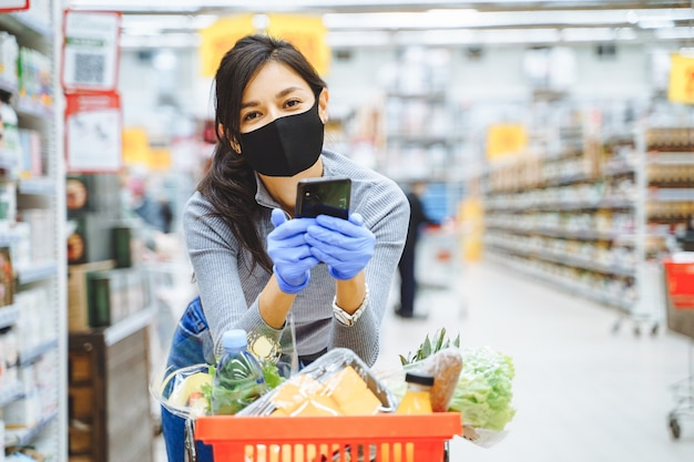 Portrait of smiling young woman in protective mask and gloves holding smartphone in hands while shopping in supermarket.