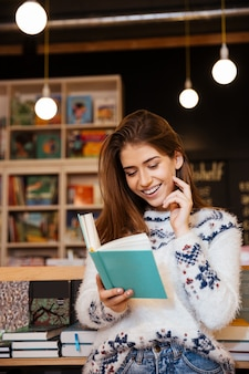 Portrait of smiling young woman reading book and talking on mobile phone