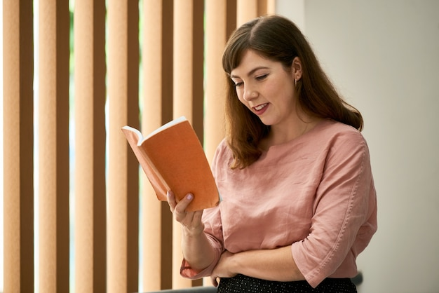 Portrait of smiling young woman reading interesting book of stories