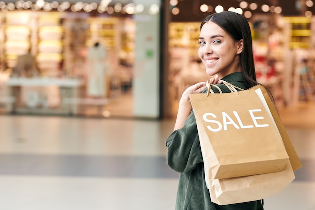 Portrait of smiling young woman satisfied with purchases holding heap of paper bags on shoulder in mall