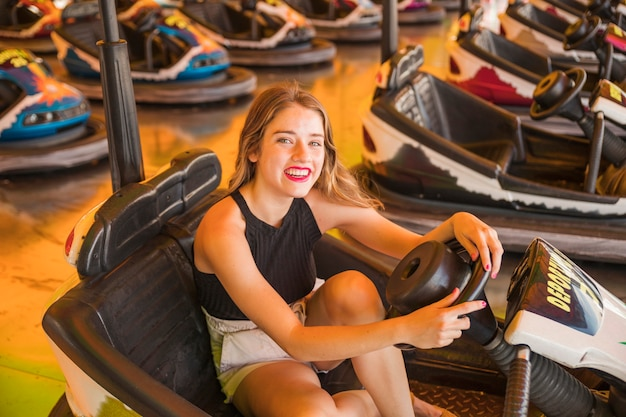 Portrait of smiling young woman sitting in the bumper car