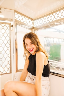 Portrait of smiling young woman sitting in the ferris wheel cabin