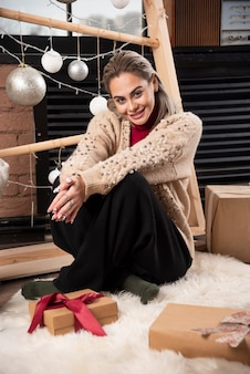 Portrait of smiling young woman sitting on the floor with presents high quality photo