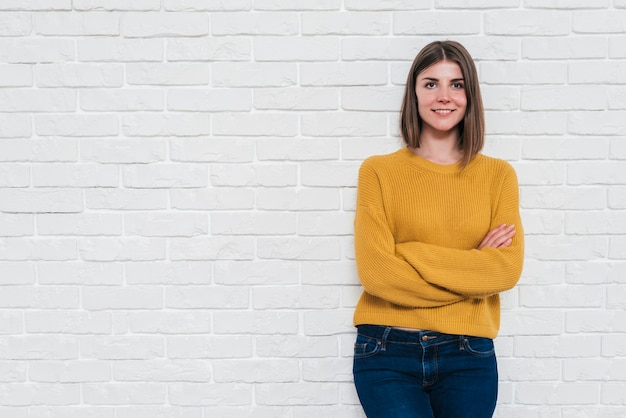 Portrait of a smiling young woman standing against white wall looking at camera