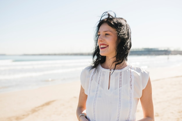 Portrait of a smiling young woman standing near the sea at beach