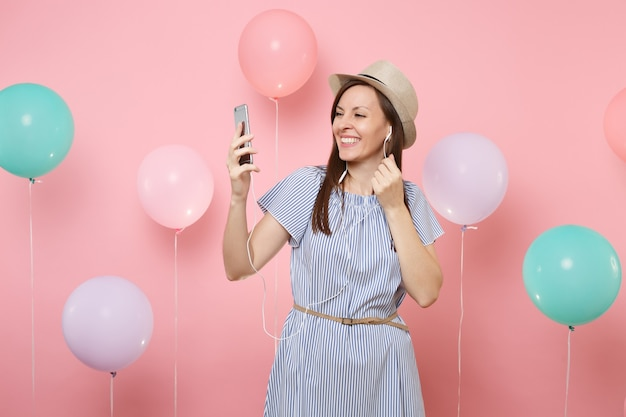 Portrait of smiling young woman in straw summer hat blue dress with mobile phone and earphones listening music making video call on pink background with colorful air balloons. birthday holiday party.