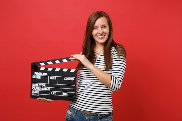 Portrait of smiling young woman in striped clothes holding classic black film making clapperboard isolated on bright red wall background. people sincere emotions lifestyle concept. mock up copy space.