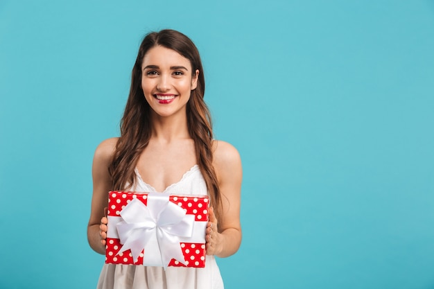 Portrait of a smiling young woman in summer dress holding a gift box