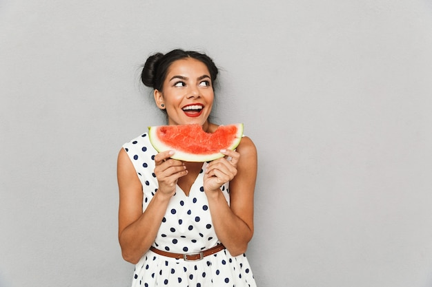 Portrait of a smiling young woman in summer dress isolated, holding watermelon slice
