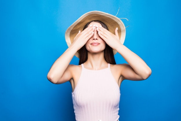 Portrait of a smiling young woman in summer hat covering eyes with her arms isolated over blue wall.