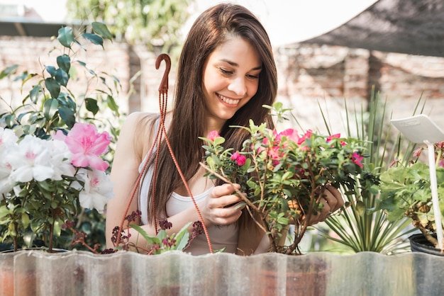 Portrait of a smiling young woman taking care of flowering plant in the garden