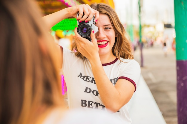 Portrait of a smiling young woman taking picture of her friend
