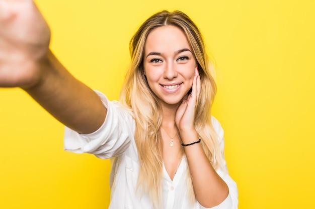 Ritratto di una giovane donna sorridente che cattura un selfie sopra la parete gialla