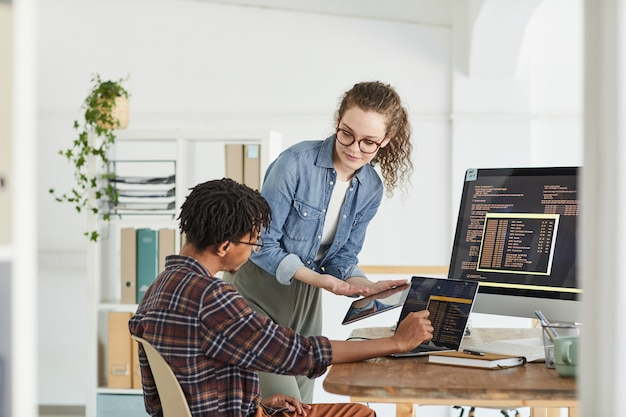 Portrait of smiling young woman talking to african-american man writing code while working in web development studio, copy space