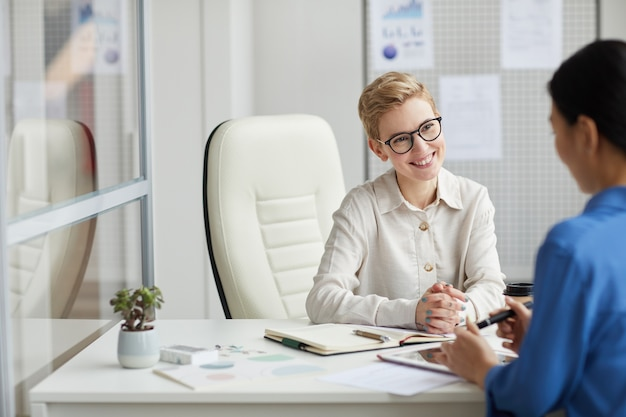 Portrait of smiling young woman talking to client or partner while working at desk in office cubicle, copy space