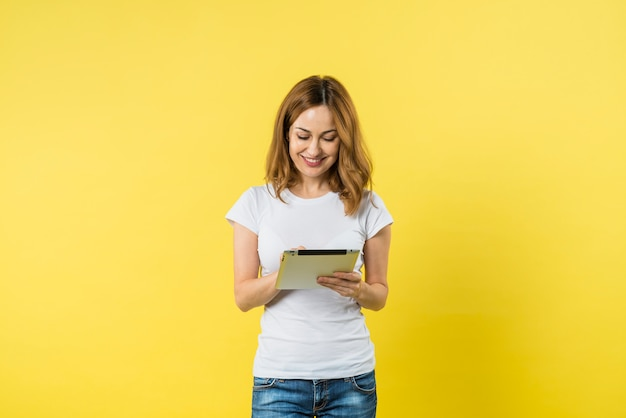 Portrait of a smiling young woman using digital tablet against yellow background