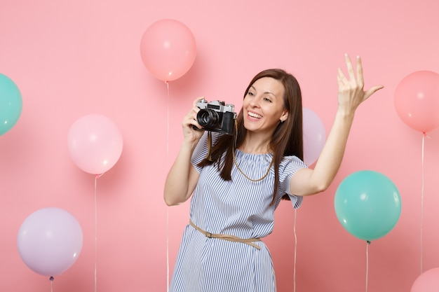 Portrait of smiling young woman wearing blue dress holding retro vintage photo camera waving hand on pink background with colorful air balloons. birthday holiday party people sincere emotions concept.
