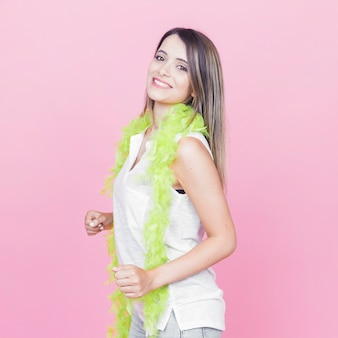 Ritratto di una giovane donna sorridente che indossa boa verde intorno al collo