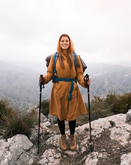Portrait of a smiling young woman with backpack holding hiking stick standing on the top of mountain