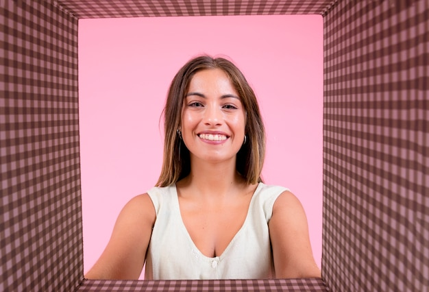 Portrait of smiling young woman with chequered background