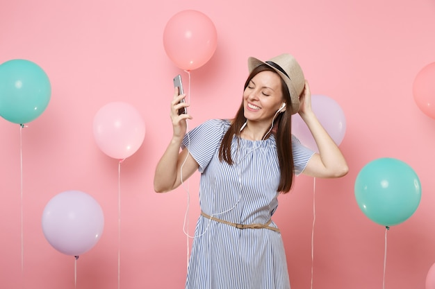 Portrait of smiling young woman with closed eyes in straw summer hat blue dress with mobile phone and earphones listening music on pink background with colorful air balloons. birthday holiday party.
