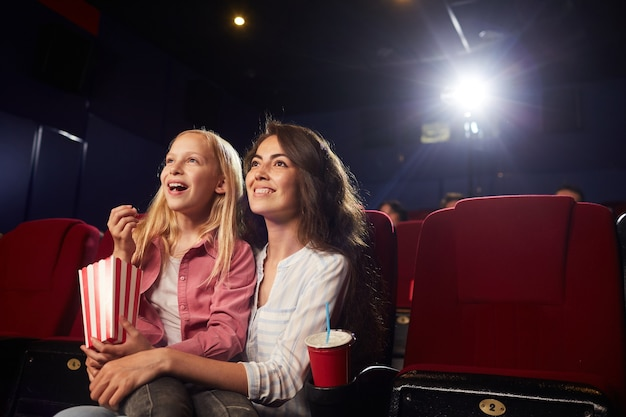 Portrait of smiling young woman with cute daughter watching cartoons in cinema while looking up at screen and enjoying popcorn, copy space