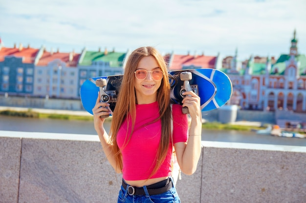 Portrait of a smiling young woman with long hair in pink glasses with a skateboard on her shoulders in the summer outdoors on a city street in a park. concept of active recreation, healthy lifestyle.