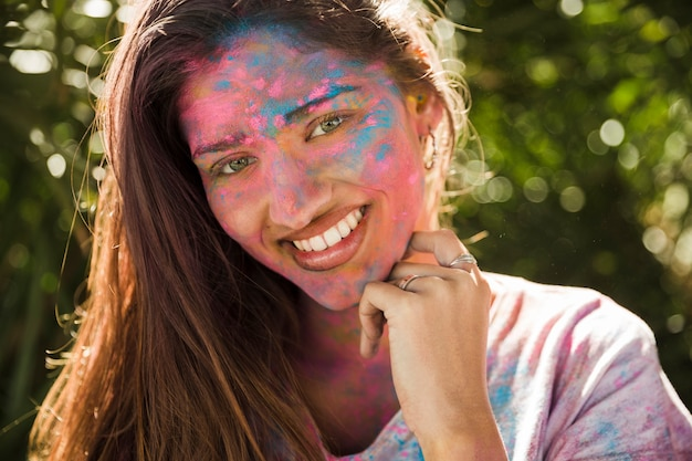 Portrait of a smiling young woman with pink and blue holi powder on her face in sunlight
