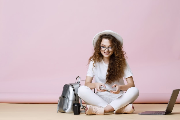 Portrait of smiling young woman with smartphone in hands