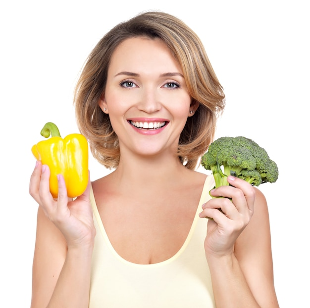 Ritratto di una giovane donna sorridente con verdure isolato su bianco.