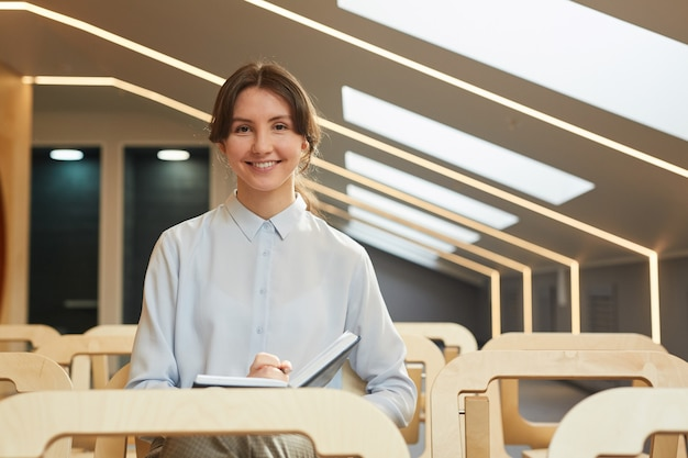 Portrait of smiling young woman writing in note pad and looking at camera while sitting in audience of empty conference hall interior, copy space