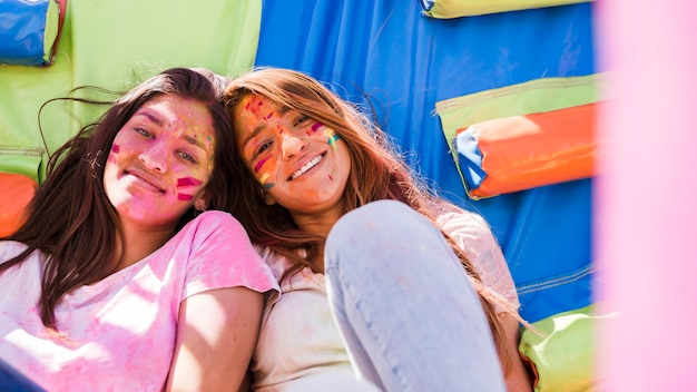 Portrait of a smiling young women with holi color paint on their face looking at camera