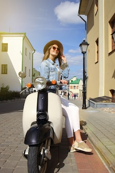 Portrait smilling beautiful girl sitting on retro scooter.