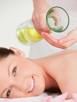 Portrait of a smilling woman getting massage oil on her back in a spa