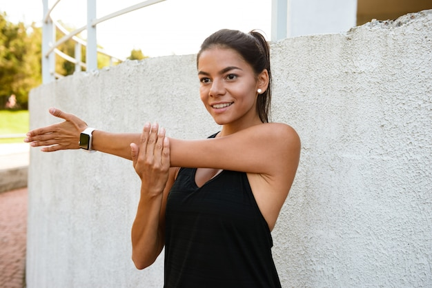 Portrait of a smilng fitness woman stretching her hands