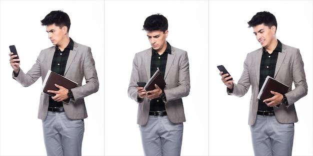 肖像画のスナップフィギュア、スーツの濃い緑色のシャツの灰色のズボンに立つ白人ビジネスマン、彼は自信を持ってデジタルスマート携帯電話を手に読んで、白い背景の上のコラージュグループパックを分離しました