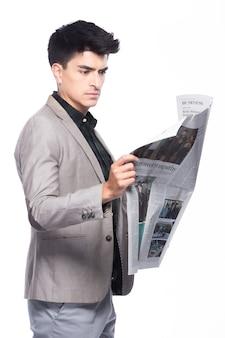 肖像画スナップフィギュア、スーツの濃い緑色のシャツの灰色のズボンに立つ白人ビジネスマン、彼は自信を持って、白い背景の上の紙の英語の新聞を読んでいます