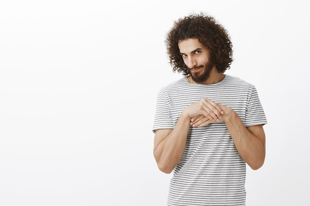 Portrait of sneaky good-looking curly-haired man with beard, rubbing palms near chest, looking from under forehead with curious expression, having bad intentions and ideas