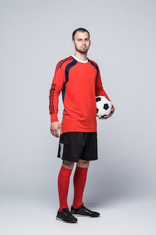 Portrait of soccer player in red shirt isolated on white