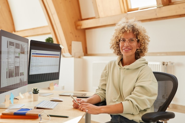 Portrait of software developer sitting at her workplace witn computers and smiling at camera at office