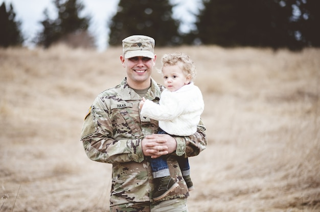 Ritratto di un padre soldato che tiene suo figlio in un campo