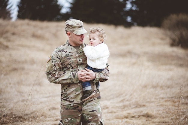 Portrait of a soldier father holding his son in a field