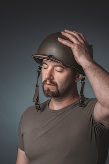Portrait of a soldier with his hand on his helmet and his eyes closed