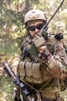 Portrait of soldiers in vest with necessary tools sending message through walkie-talkie in forest
